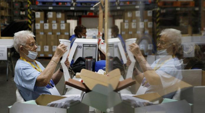 Election workers process mail-in ballots