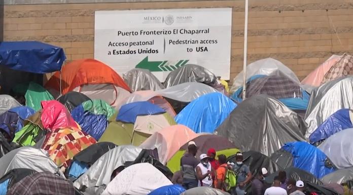 Migrants wait in tents